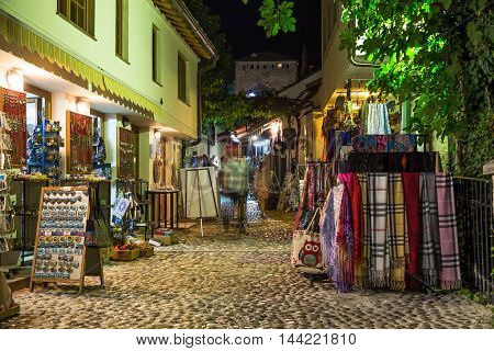 MOSTAR BOSNIA AND HERZEGOVINA - 15TH AUGUST 2016: A view along Jusovina street in Mostar at night. The outside of shops and the blur of people can be seen.