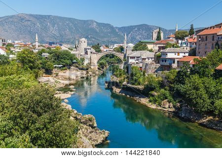 A view of the Mostar skyline during the day towards the Old Bridge (Stari Most). Buildings and the River Neretva can be seen.