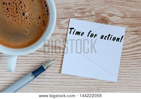 TIME FOR ACTION writting on paper near cup of morning coffee at workplace or wooden table.