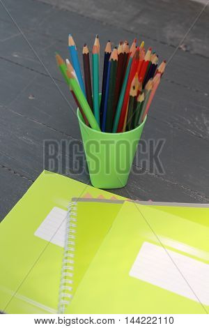 Green notebook and colored pencils in a glass
