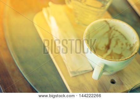 Empty cup of coffee on wooden table ( Filtered image processed vintage effect. )