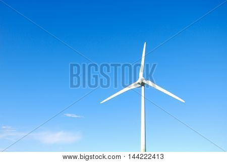 One windturbine by a bright blue sky