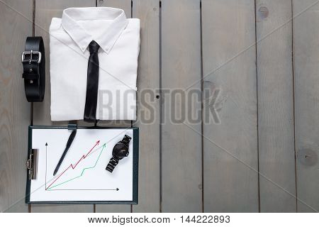 Businessman, Work Outfit On Grey Wooden Background. White Shirt With Black Tie, Belt, Planchette. Ba