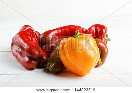 Closeup yellow and red sweet peppers on white wooden background
