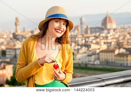 Young smiling woman in yellow holding pendant in form of the heart on the old town background in Florence