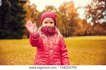 autumn, childhood, gesture, nature and people concept - happy little girl waving hand in park