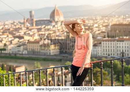 Young woman in sportswear feeling tired after morning exercise on the old city background in Florence in Italy