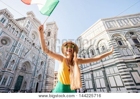 Young smiling female traveler standing with italian flag in front of the famous Santa Maria del Fiore cathedral in Florence. Promoting tourism in Italy