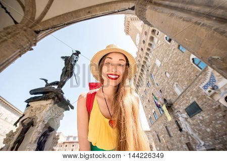 Young female traveler smiling in front of the Vecchio palace in Florence.