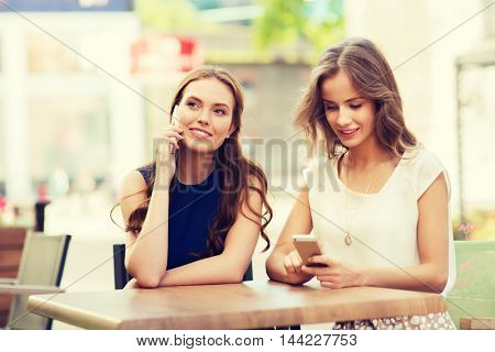 technology, lifestyle, friendship, communication and people concept - happy young women or teenage girls with smartphones at cafe outdoors