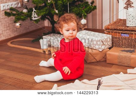 Happy pretty baby dressed in red dress with Christmas gifts