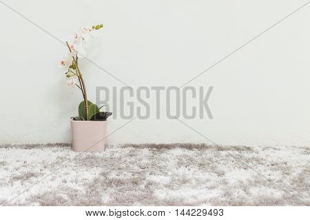 Closeup artificial plant with white orchid flower in pink pot on blurred gray carpet and white cement wall textured background under window light