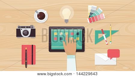 Designer desktop with camera swatches and work tools a designer is using apps on a touch screen tablet