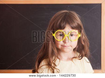 Smart kid wearing a yellow glasses stood in front of a blackboard