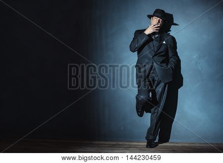 Retro 1940 Film Noir Gangster Wearing Suit And Hat. Smoking Cigarette. Standing Against Wall.