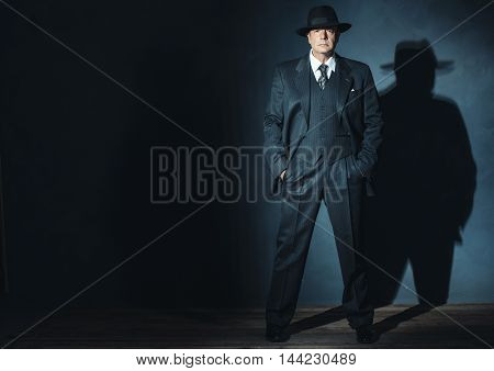 Retro 1940 Gangster Standing In Front Of Gray Wall.