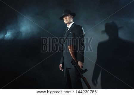 Retro 1940S Film Noir Gangster Standing With Gun.