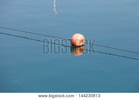 Red round buoy in the sea to signal