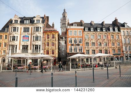 Lille France - 2015 December 27 : The Grand-Place of Lille with the tower of the chamber of commerce in the background and pedestrians walking in front of houses