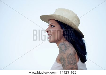 Brunette woman with straw hat and tattoo on the arm looking forward