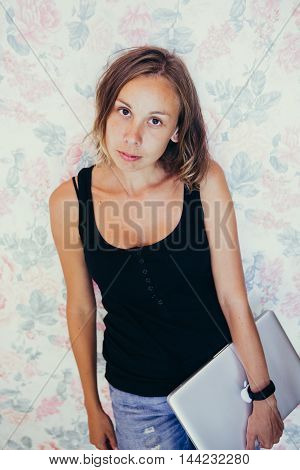 SOCHI, RUSSIA - JULE 29, 2016: Portrait of attractive young woman with short hair holding apple laptop and looking calmly at camera.Floral background.