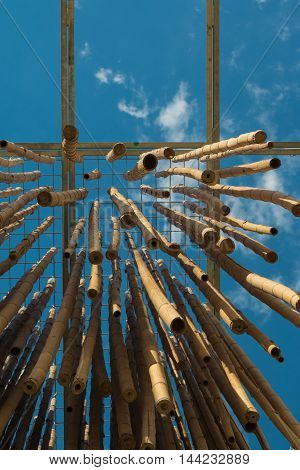 MILANO, ITALY - MAY 2015: Hanging Bamboo Canes Close Each Other Blue Sky in background at Milan Exposition 2015 - Italy