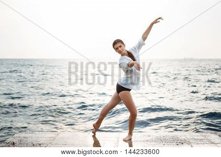 Young beautiful ballerina dancing and posing outside early in morning, sea background.