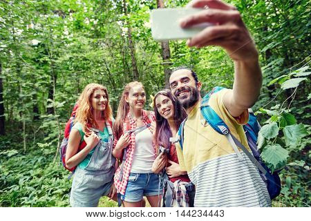 technology, travel, tourism, hike and people concept - group of smiling friends walking with backpacks taking selfie by smartphone in woods