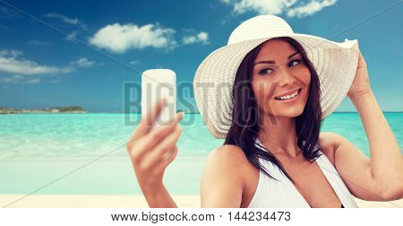 travel, summer, technology and people concept - sexy young woman taking selfie with smartphone over tropical beach background