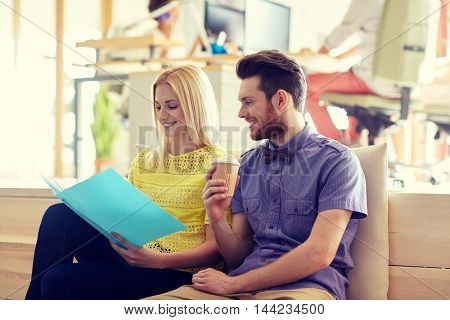 business, startup and people concept - happy man and woman with folder drinking coffee in office