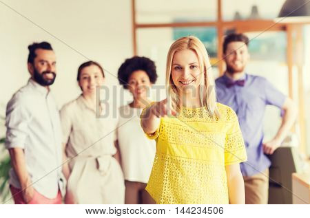business, startup, people, gesture and teamwork concept - happy young woman pointing finger at you over creative team in office