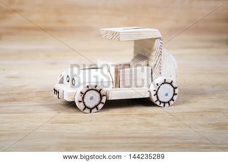 Hand-made wooden car in wood background.Children's article.