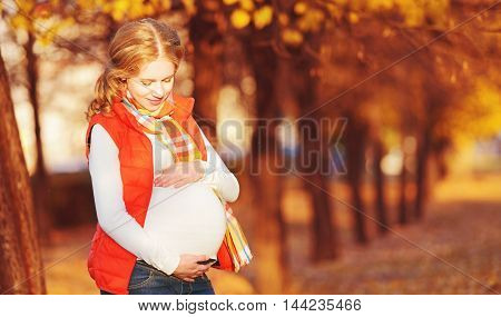 Happy pregnant woman on autumn walk in nature