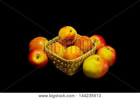 summer peach ripe fruit in a wicker bowl with red apples on a dark background