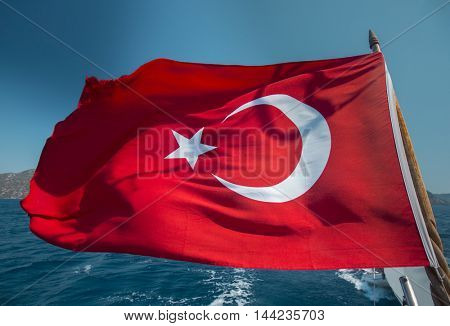 Turkish flag of a boat waving in Mediterranean shores of Turkey