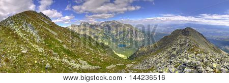 Summer mountain landscape in a panoramic photograph. View of the beautiful valley and pond in High Tatra Mountains Slovakia.