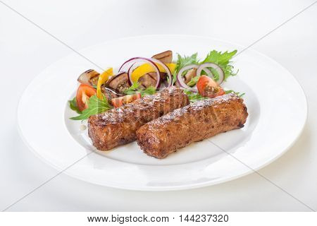 lula kebab with vegetables fresh tomato cucumber onion salad on a plate on a white background isolated Beautiful