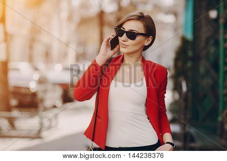 spectacular young brunette outside fashionable and healthy use the phone
