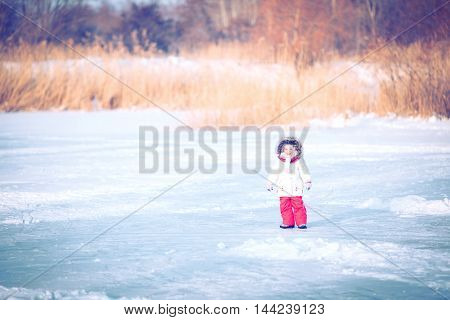 Little girl enjoying a sleigh ride. Child sledding. Toddler kid riding a sledge.