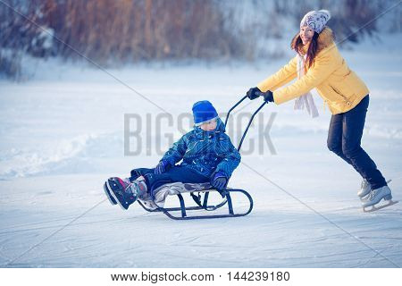 Little girl enjoying a ride on a sled. Children sledding. Toddler baby rides in a sleigh. Children playing outdoors in the snow.