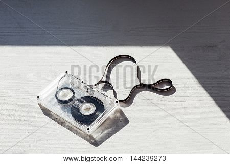 audio tape and shadow on wooden background