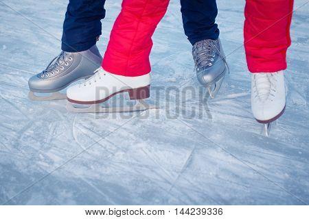 Family having fun at the outdoor skating rink in winter.