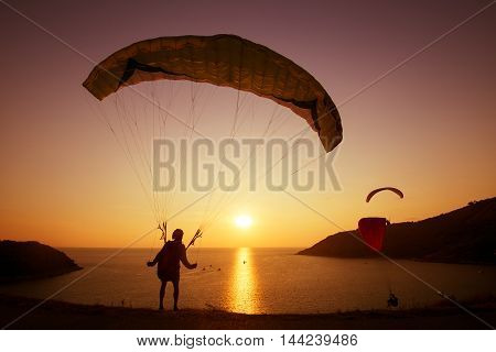 Skydiver preparing to start flying over the bay on background of sunset sky. Phuket island, Thailand