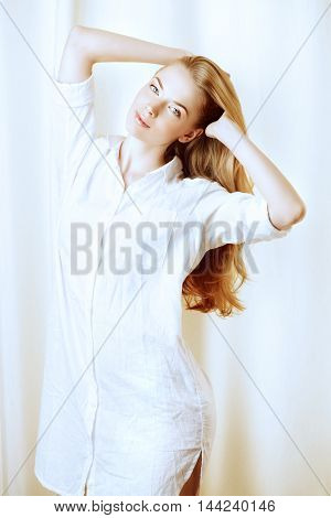 Happy young woman at home. Beautiful blonde woman standing by the window in her room.