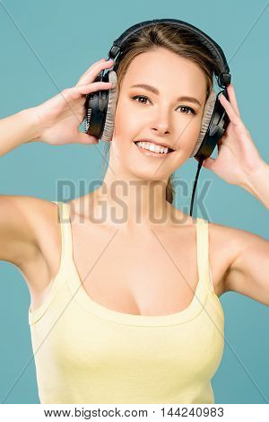 Modern girl enjoys listening to music in headphones. Positive emotions, leisure. Copy space.