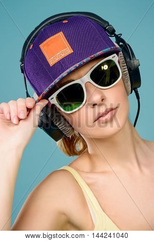 Modern young woman enjoys listening to music in headphones. Positive emotions, leisure. Copy space.