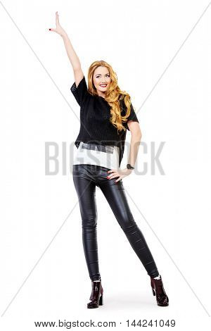 Joyful pretty woman wearing stylish clothes smiling and dancing. Full length portrait. Isolated over white.