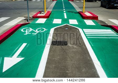 Bike lane city. Sign for bicycle painted on the asphalt colored. Car and traffic in background. Dividing line diminishing perspective.