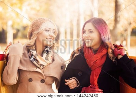 Beautiful girls walking in park with colorful bags. Sunny autumn day. Discounts concept.