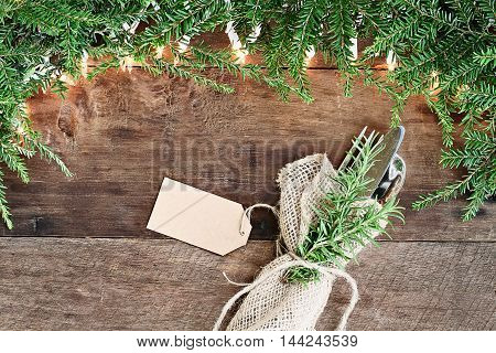 Christmas tree pine branches silverware wrapped in a burlap napkin with blank card and decorative lights over a rustic background of barn wood. Image shot from overhead.